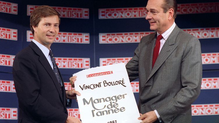 """Le Premier ministre de l'époque, Jacques Chirac, remet le 14 octobre 1987 à Paris le prix de Manager de l'année, décerné par """"Le nouvel Economiste"""" à Vincent Bolloré, président de l'entreprise Bolloré Technologies. (JOEL ROBINE / AFP)"""