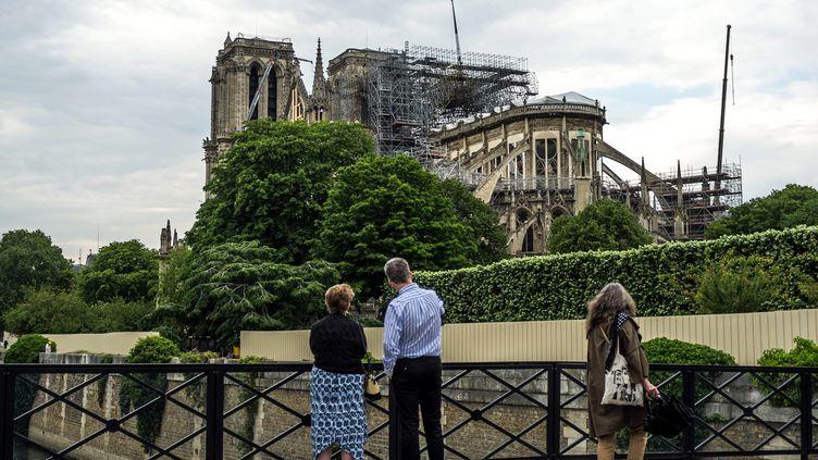 Des passants devant la cathédrale Notre-Dame de Paris, le 21 mai 2019. (BRUNO LEVESQUE / MAXPPP)