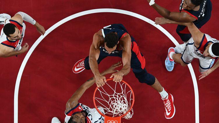 Le dunk de Rudy Gobert (au centre) face à Kevin Durant, lors de la finale des Jeux olympiques du tournoi de basket entre la France et les Etats-Unis, le 7 août 2021. (ARIS MESSINIS / AFP)
