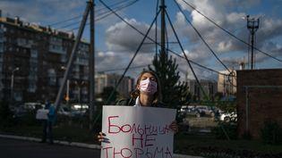 """Une femme tient une pancarte où l'on peut lire en russe """"un hôpital n'est pas une prison"""", devant l'hôpital d'Omsk où a été admis l'opposant Alexeï Navalny après des soupçons d'empoisonnement. (DIMITAR DILKOFF / AFP)"""