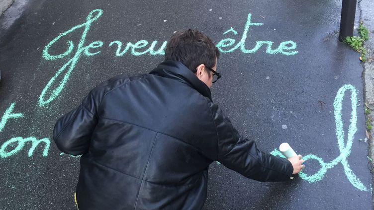 """Claudie, alias la street artiste Achbé, """"craieant"""" un de ses messages sur un trottoir de Montmartre en janvier 2018.  (Laure Narlian / Culturebox)"""