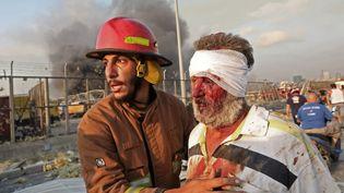 Un pompier prend en charge une victime de l'explosion, le 4 août 2020 à Beyrouth (Liban). (ANWAR AMRO / AFP)