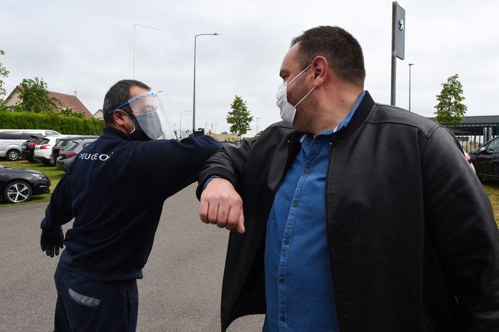 Un concessionnaire automobile et un client se saluent du coude, lors de l'épidémie de Covid-19, le 4 mai 2020 à Illiers-Combray (Eure-et-Loir). (JEAN-FRANCOIS MONIER / AFP)