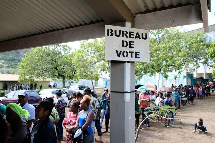 Des personnes attendent devant un bureau de vote, le 4 octobre 2020, à Nouméa. (THEO ROUBY / AFP)