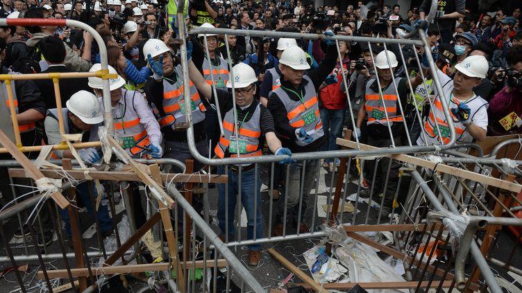 Des employés démontent les barricades des manifestants prodémocratie, le 11 décembre 2014, à Hong Kong. (DALE DE LA REY / AFP)
