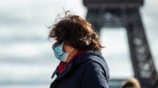Une femme se protège le visage avec un masque près de la tour Eiffel, à Paris (photo prise le 31 janvier 2020). (AFP)