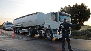 Un policier oriente des camions-citernes vers le dépôt de carburant de Fos-sur-Mer (Bouches-du-Rhône), après la levée du blocage par les forces de l'ordre, le 24 mai 2016. (BORIS HORVAT / AFP)