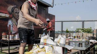 """Écrivain et décorateur de basketsRasik """"Mr.ëksê""""Greendevant sa dernière œuvre d'art à Maboneng, Johannesburg, le 11 février 2021 (LUCA SOLA / AFP)"""
