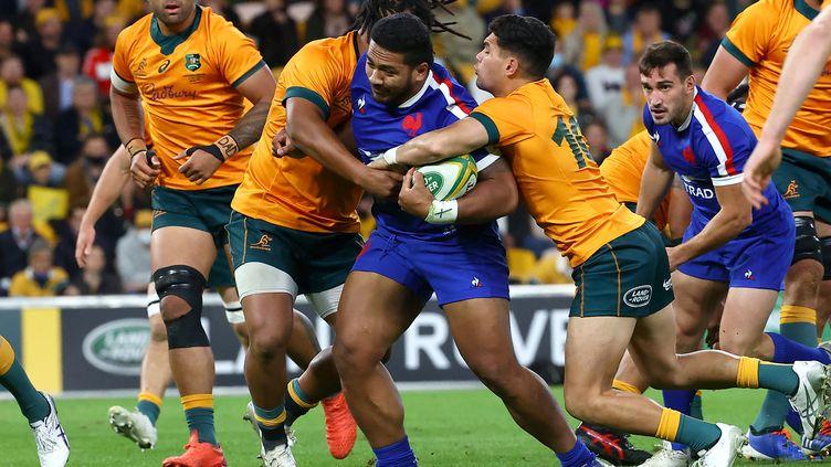 Sipili Falatea pris par les AustraliensNoah Lolesio etBrandon Paenga-Amosa, lors du troisième test-match entre lAustralie et la France, le 17 juillet à Brisbane. (PATRICK HAMILTON / AFP)
