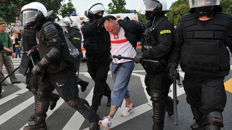 Un supporter polonais est interpellé à Varsovie (Pologne) lors d'incidents avant le match Pologne-Russie, mardi 12 juin 2012. (VLADIMIR PESNYA / RIA NOVOSTI / AFP)