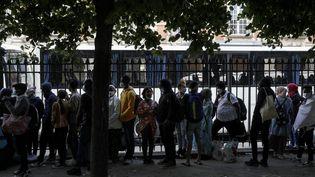 Des personnes sans-abri attendent d'être relogées, à Paris, le 30 juillet (GEOFFROY VAN DER HASSELT / AFP)