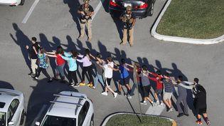 Après la fusillade, les élèves ont été évacués en file indienne de ce lycée deParkland en Floride (Etats-Unis), le 14 février 2018. (JOE RAEDLE / GETTY IMAGES NORTH AMERICA / AFP)