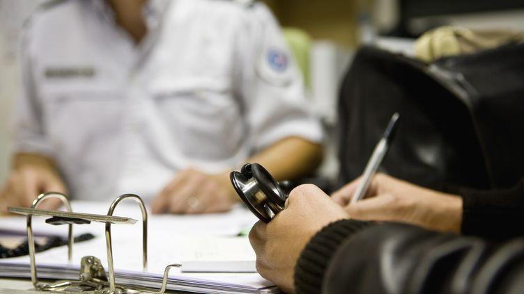 Un médecinaccompagné d'un policier remplit un formulaire (illustration). (JAMES HARDY  / MAXPPP)