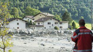 Un secouriste devant le village de Bondo (sud-est de la Suisse), balayé par un glissement de terrain, le 23 août 2017. (GIANCARLO CATTANEO / AFP)