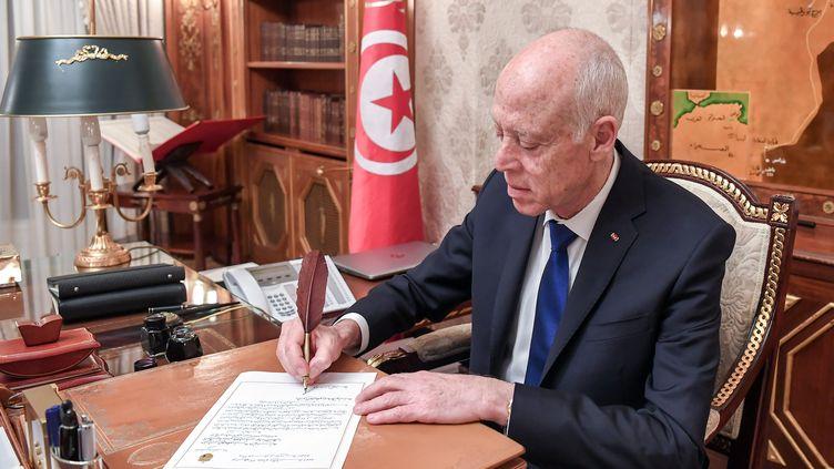 Le chef de l'Etat tunisien, Kaïs Saïed, en train d'écrire une lettre dans son bureau au palais présidentiel de Carthage, le 19 février 2020. (AFP - TUNISIAN PRESIDENCY)