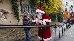 Le père Noël croise un enfant dans le 18e arrondissement de Paris, le 20décembre 2017. (ELODIE DROUARD / FRANCEINFO)