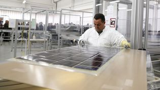Un technicien vérifie des plaques photovoltaïques dans une usine à Tourouvre (Orne). (CHARLY TRIBALLEAU / AFP)