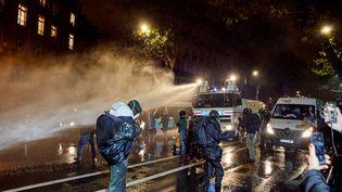 """Des personnes filment devant les canons à eau de la police, lors de la manifestation contre la proposition de loi sur """"la sécurité globale"""", le 17 novembre 2020 à Paris. (ADNAN FARZAT / NURPHOTO VIA AFP)"""