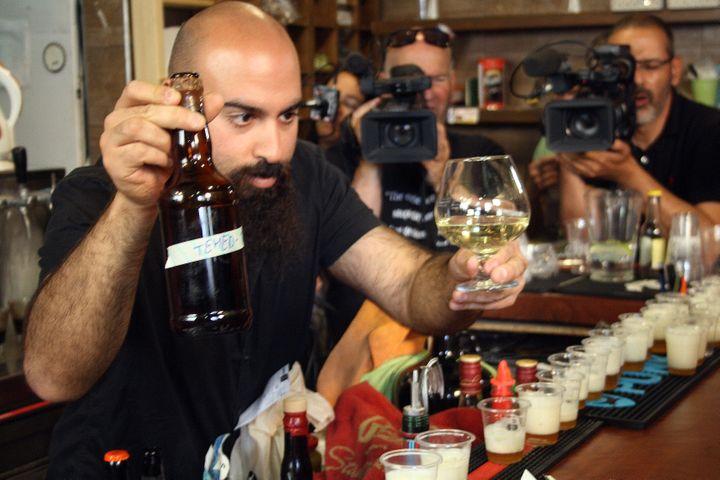 Shmuel Nakai, propriétaire du Biratenu Bar, savoure un hydromel et une bière issus de levures vieilles de plusieurs milliers d'années, mercredi 22 mai 2019 à Jérusalem (Israël). (ROBERT MESSER / DPA / AFP)