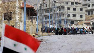 Un drapeau syrien flotte sur une barricade à l'entrée de Madaya (Syrie), le 14 janvier 2016. (LOUAI BESHARA / AFP)