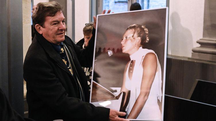 Jacky Kulik montre une photo de sa fille, Elodie Kulik, au tribunal d'Amiens (Somme), le 21 novembre 2019. (DENIS CHARLET / AFP)