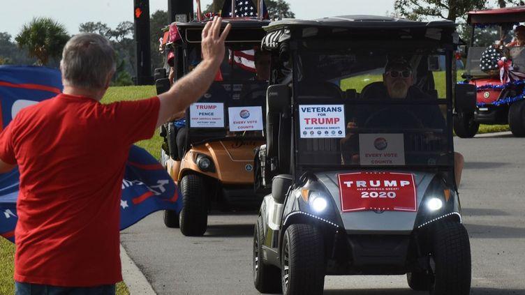 Des retraités américains manifestent pour la réelection de Donald Trump dans de petites voiturettes de golf, le 3 octobre en Floride. (PAUL HENNESSY / NURPHOTO / AFP)