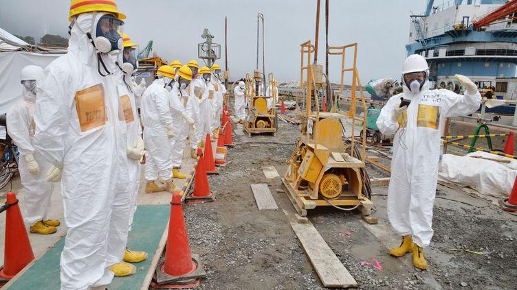 Des experts et des élus en train d'inspecter les installations censées contenir les fuites d'eau radioactives, le 6 août 2013, à la centrale nucléaire de Fukushima (Japon). (KYODO KYODO / REUTERS)