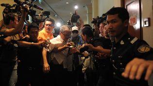 Des proches des passagers chinois du vol MH370, expulsés de la salle où s'est tenue la conférence de presse du ministre des Transports à Kuala Lumpur (Malaisie), le 19 mars 2014. (MOHD RASFAN / AFP)