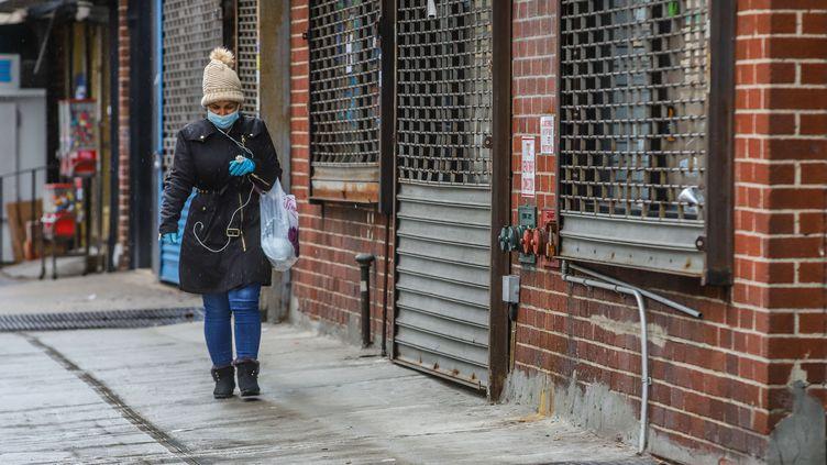 Une femme avec un masque de protection marche dans le quartier deManhattan, à New York, le 28 mars 2020. (VANESSA CARVALHO / BRAZIL PHOTO PRESS / AFP)