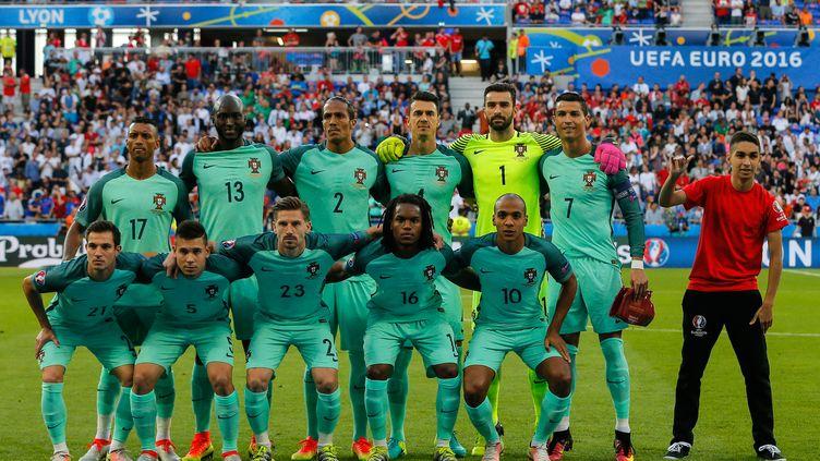 L'équipe du Portugal et un volontaire de l'Euro, juste avant le coup d'envoi de la demi-finale contre le pays de Galles à Lyon, le 6 juillet 2016. (VLADIMIR PESNYA / SPUTNIK / AFP)