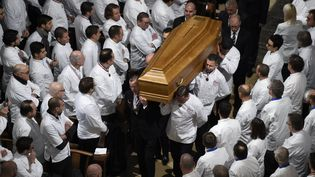 Des chefs portent le cercueil de Paul Bocuse et d'autres se recueillent en silence, vendredi 26 janvier, dans la cathédrale Saint-Jean à Lyon. (PHILIPPE DESMAZES / POOL / AFP POOL )