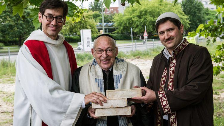 Le pasteur Gregor Hohberg, le rabbin Tovia Ben-Chorin et l'imam Kader Sanci posent la première pière de leur projet de lieu de culte commun, à Berlin (Allemagne), le 3 juin 2014. (PAULZINKEN / MAXPPP)
