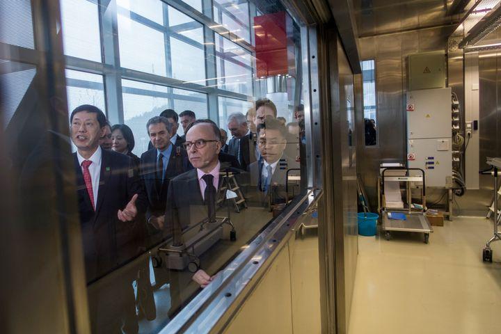 Le Premier ministre, Bernard Cazeneuve, visite le laboratoire P4 de Wuhan (Chine), le 23 février 2017. Yves Lévy, président-directeur général de l'Inserm, est présent à sa gauche à l'arrière-plan. (JOHANNES EISELE / AFP)