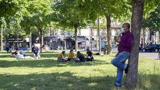 Des Parisiens sur la place Pereire, dans le 17e arrondissement de la capitale, le 18 mai 2020, en attendant la réouverture des parcs et jardins. (FRANCK RENOIR / HANS LUCAS / AFP)