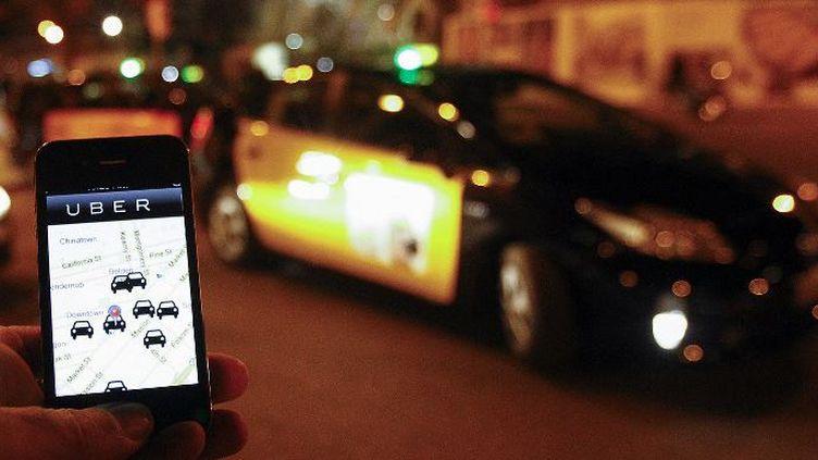 L'application Uber sur un smartphone devant un taxi à Barcelone (Espagne),le 9 décembre 2014. (AFP - QUIQUE GARCIA)