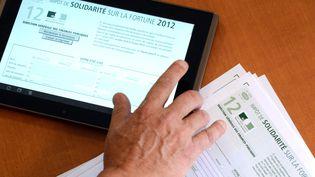 Un homme consulte sa déclaration d'impôt de solidarité sur la fortune sur sa tablette, le 19 juillet 2012 à Rennes. (DAMIEN MEYER / AFP)