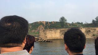 Ci-contre, des touristes chinois naviguent sur le fleuve Yalu, qui sépare la Chine et la Corée du Nord. Les habitants de cette zone frontalière commencent à s'inquiéter de l'impact environnementaldes essais nucléaires nord-coréens. (DOMINIQUE ANDRÉ / RADIO FRANCE)