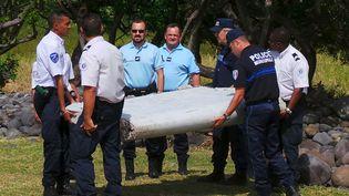 Des gendarmes et des policiers portent le débris d'avion retrouvé sur le littoral de La Réunion, mercredi 29 juillet. (PRISCA BIGOT / ZINFOS 974 / REUTERS)
