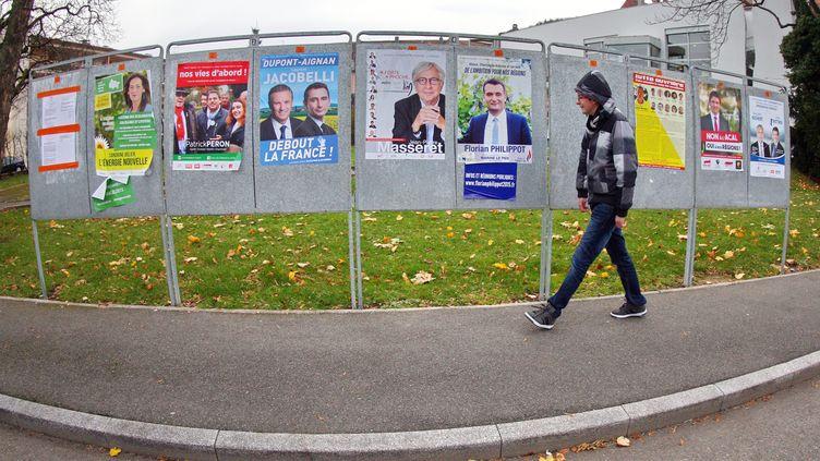 Un homme passe devant des panneaux électoraux avant les élections régionales, le 24 novembre 2015 à Thann (Haut-Rhin). (MAXPPP)