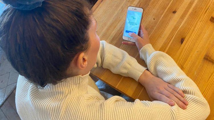 Une femme consulte l'application Covidom à Paris, le 27 mars 2020. (THOMAS PONTILLON / RADIO FRANCE)