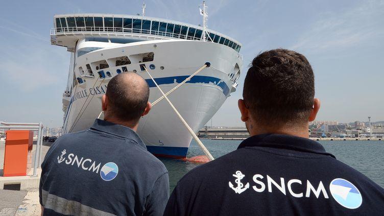 """Des employés de la SNCM devant le ferry """"Daniele Casanova"""", à l'occasion d'un grève, le 24 juin 2014 dans le port de Marseille. (BORIS HORVAT / AFP)"""