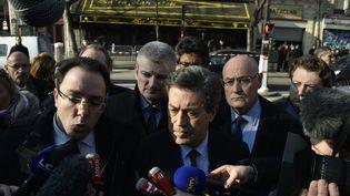 Les députés membres de la commission d'enquête parlementaire présidée par Georges Fenech (au centre) répondent aux journalistes avant d'entrer dans le Bataclan, le 17 mars 2016, dans le 11e arrondissement de Paris. (ALAIN JOCARD / AFP)