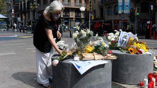 Une femme dépose des fleurs sur les Ramblas à Barcelone (Espagne), le 17 août 2020, trois ans après les attentats jihadistesqui ont tué 16 personnes. (JOSEP LAGO / AFP)