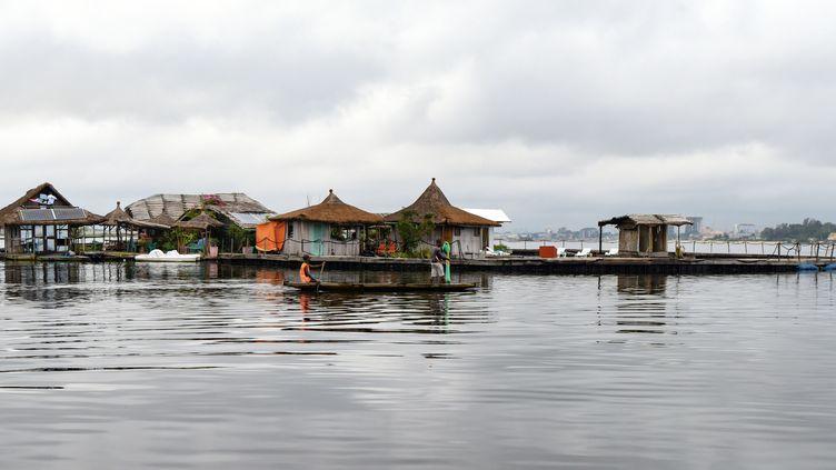 Sur cette photo, prise le 6 août 2019, des pêcheurs passent à côté d'une île artificielle constituée d'environ 700 000 déchets de plastique recyclés, dans la lagune Ebrie à Abidjan. (ISSOUF SANOGO / AFP)