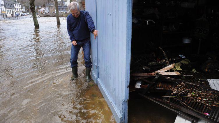 Un habitant de Quimperlé (Finistère) nettoie l'entrée de son domicile après les crues, le 3 janvier 2014. (FRED TANNEAU / AFP)