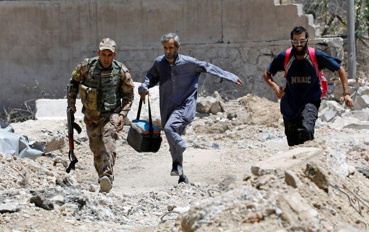 Un soldat irakien et des civils courent pour éviter les balles des snipers de l'Etat islamique, le 15 juin 2017, à Mossoul (Irak). (ERIK DE CASTRO / REUTERS)