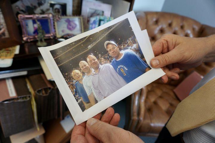 James Moschella montre une photo de lui (au centre) avec son frère John (avec une casquette). (MARIE-VIOLETTE BERNARD / FRANCEINFO)