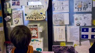 """Un enfant regarde des dessins réalisés en hommage aux victimes de """"Charlie Hebdo"""",près du siège de l'hebdomadaire, àParis, le9 janvier 2015. (  MAXPPP)"""