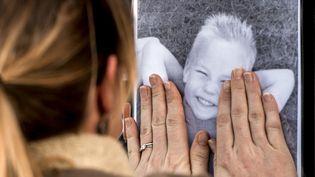 Une femme rend hommage au garçon tué après avoir reçu un palet de hockey, lors d'un rassemblement le 2 novembre 2014, à Dunkerque. (PHILIPPE HUGUEN / AFP)
