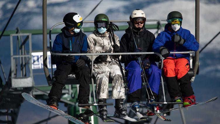 Des skieurs, certains portant un masque de protection sanitaire, sur une remontée mécanique de la station de ski de La Masella, en Catalogne (Espagne), le 14 décembre 2020. (JOSEP LAGO / AFP)